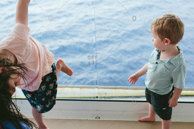 Children standing on the deck by a glass railing on a cruise ship