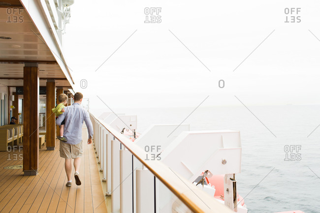 Man carrying toddler on the deck of a cruise ship