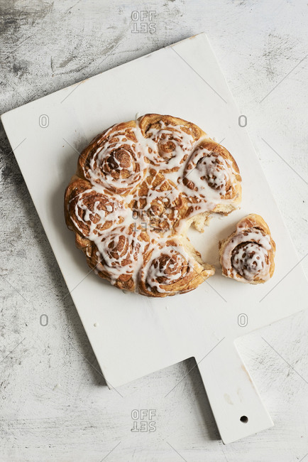 One cinnamon roll pulled from the bunch on cutting board