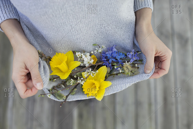 Woman holding spring flowers in her sweater