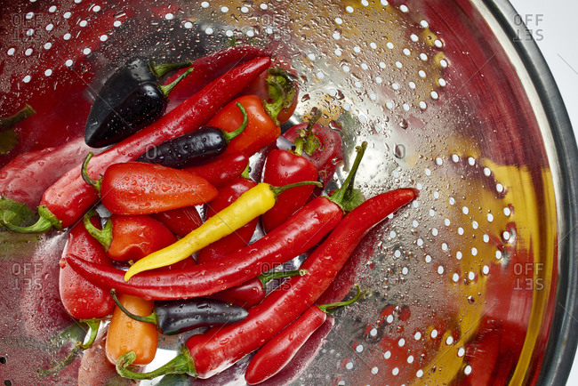 Colorful fresh peppers being rinsed in a colander