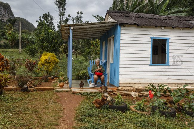 Pinar del Rio, Cuba - January 23, 2016: Woman sitting on the porch of her house in Parque Nacional Vi_ales, Cuba