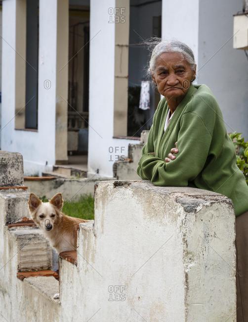 Havana, Cuba - January 20, 2016: Elderly woman with her dog at Vedado neighborhood, Havana, Cuba