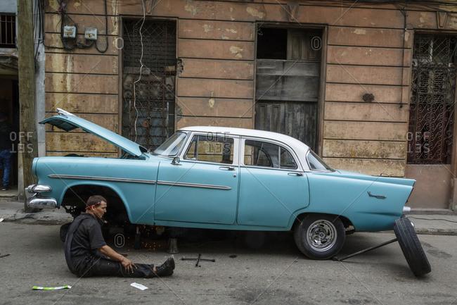 Havana, Cuba - January 21, 2016: Man fixing an old vintage car in Centro Havana, Cuba