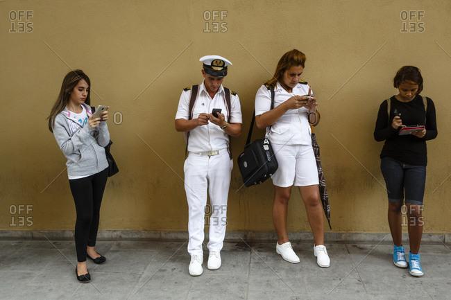 Havana, Cuba - January 21, 2016: Young people using their mobile phones, Havana, Cuba