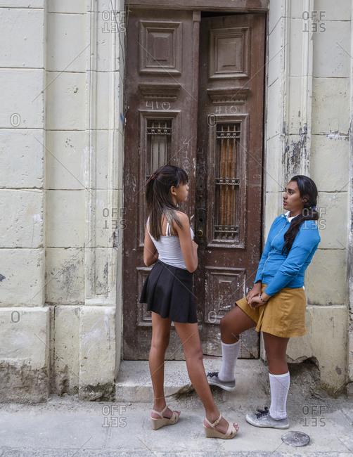 Havana, Cuba - January 21, 2016: Two female teenagers talking infant of entryway in Centro Havana, Havana, Cuba