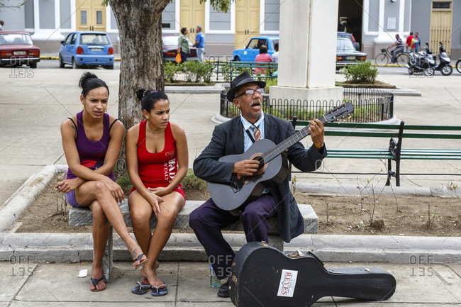 Bay of Pigs, Cuba - January 26, 2016: Man singing and playing guitar on bench next to two women at Parque Jose Marti, Cienfuegos, Cuba