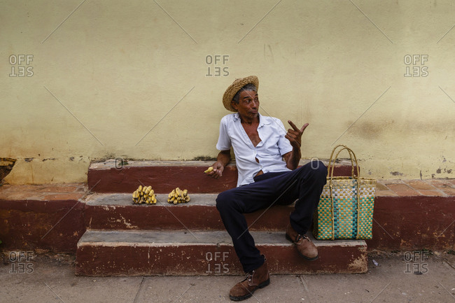 Trinidad, Cuba - January 28, 2016: Man selling bananas on steps, Trinidad, Cuba