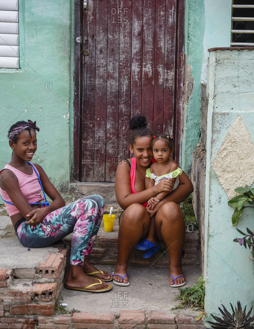 Trinidad, Cuba - January 29, 2016: Young girls siting on the steps of house, Trinidad, Cuba