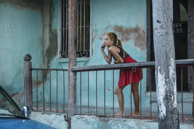 Santiago de Cuba, Cuba - February 3, 2016: Teenager woman standing at a balcony at the Tivoli neighborhood, Santiago de Cuba, Cuba