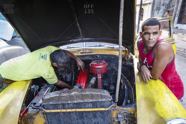 Santiago de Cuba, Cuba - February 3, 2016: Men fixing an old vintage car at Tivoli neighborhood, Santiago de Cuba, Cuba
