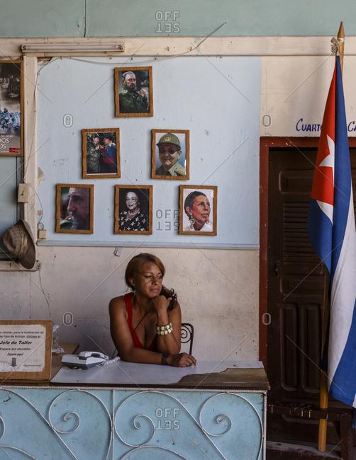 Santiago de Cuba, Cuba - February 3, 2016: Receptionist sitting at desk at governmental carpentry, Santiago de Cuba, Cuba