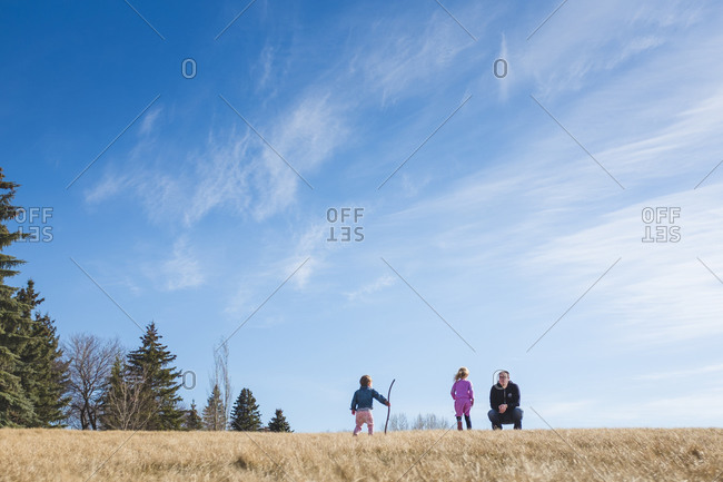 Two girls and their father playing in a grassy field