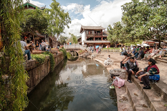People gathered along a small canal in Lijiang, China