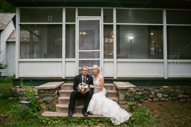 Bride and groom siting on the steps in front of a screened porch