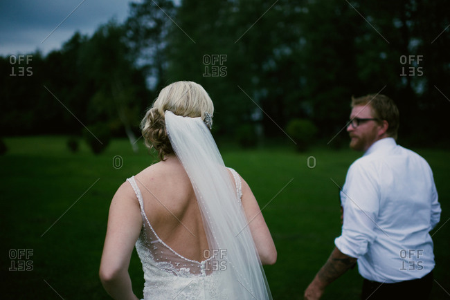 Back view of bride and groom walking at night