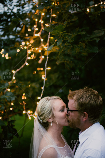 Bride and groom kissing in front of trees with twinkle lights