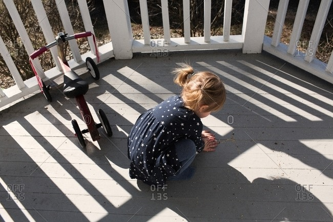 Toddler girl playing on a deck next to a tricycle