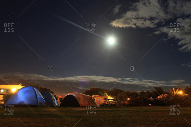 Camping tents and RVs under a full moon at a holiday park in Kaikora, New Zealand