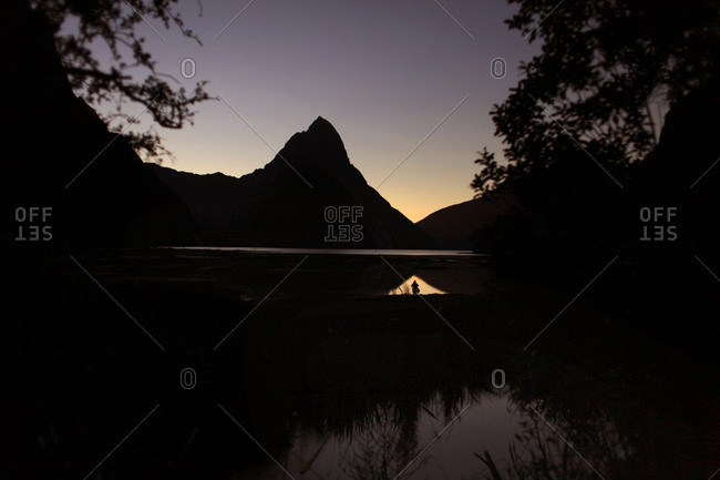 A photographer takes pictures of Mitre Peak at sunset in New Zealand