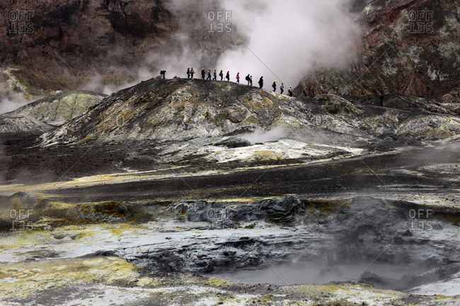 Tourists crossing a ridge on White Island, New Zealand with steam rising around them