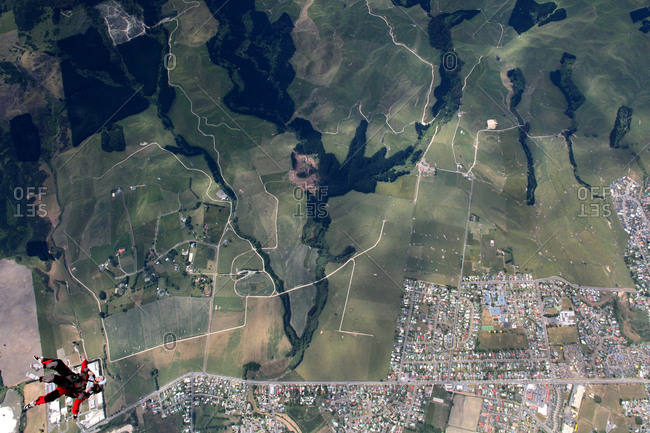 Skydivers over a patchwork of fields and neighborhoods near Rotorua, New Zealand