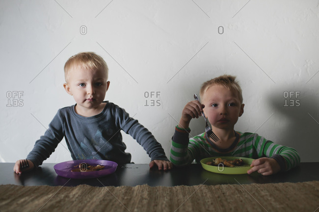 Boys staring while eating at table