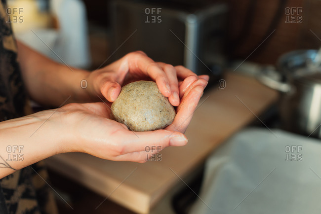 Person holding a ball of dough