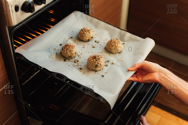 Person putting balls of dough into the oven