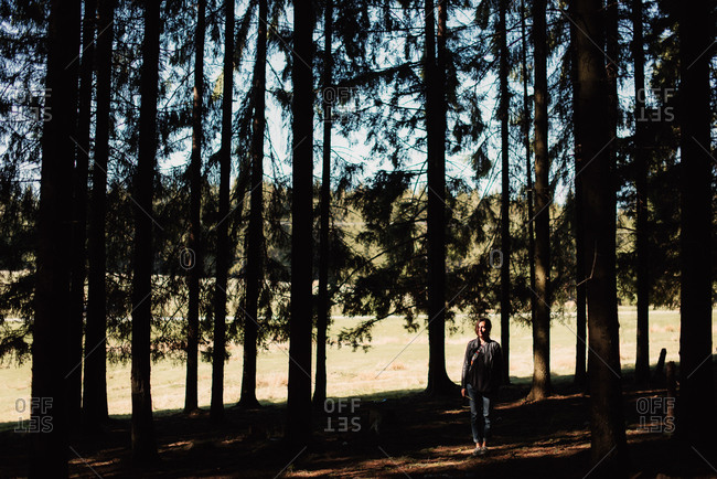 Woman standing by tall shady trees