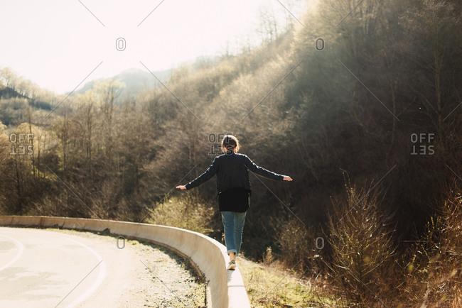 Woman walking on a cement guardrail