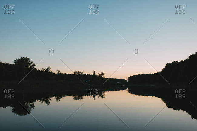 Silhouette and reflection of land surrounding a lake