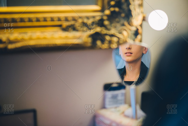 Reflection of a woman in a small mirror