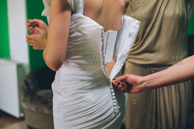 Bride having her wedding dress zipped up