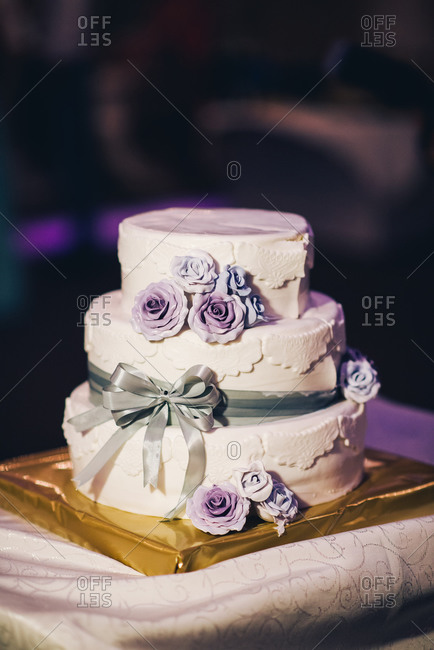 Wedding cake with purple frosting roses