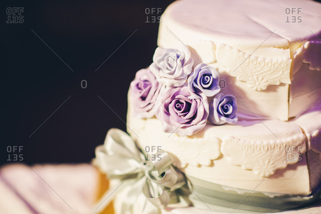 Close up of a wedding cake with purple frosting roses