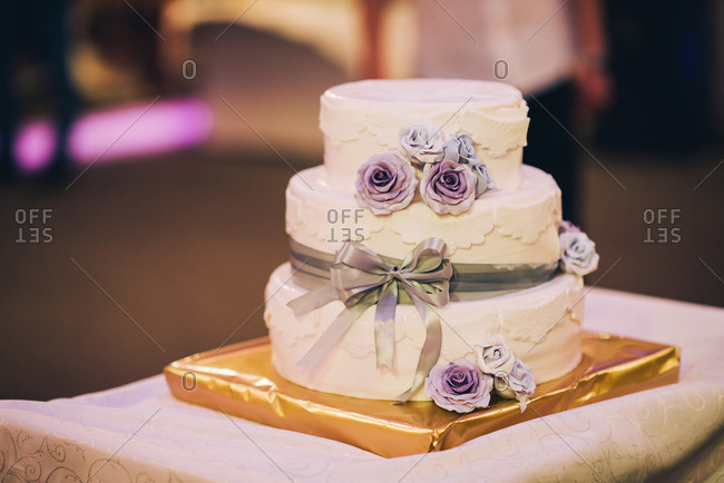 Wedding cake with purple frosting roses and green ribbon