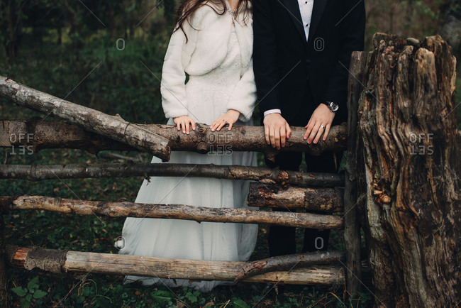 Bride and groom standing by a fence made of tree logs