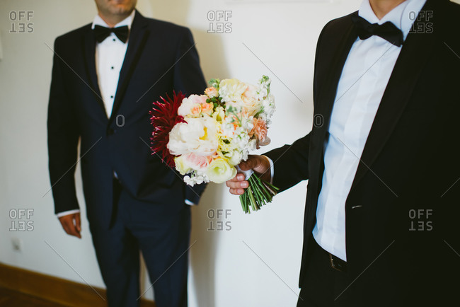 Man holding bouquet of flowers before a wedding