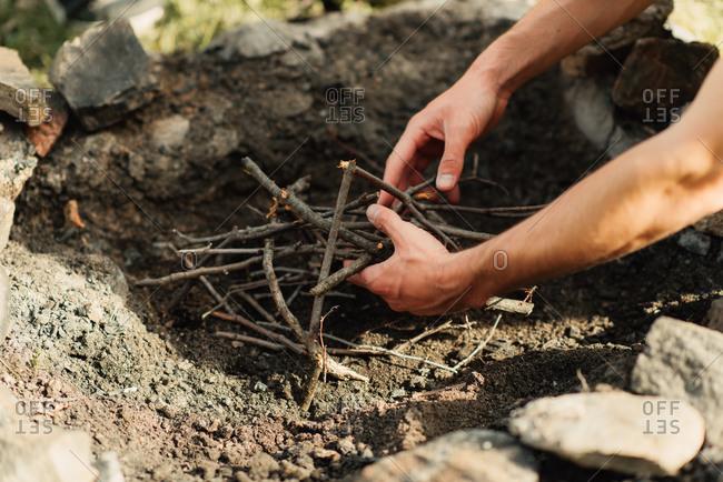 Close up of man putting sticks into a fire pit