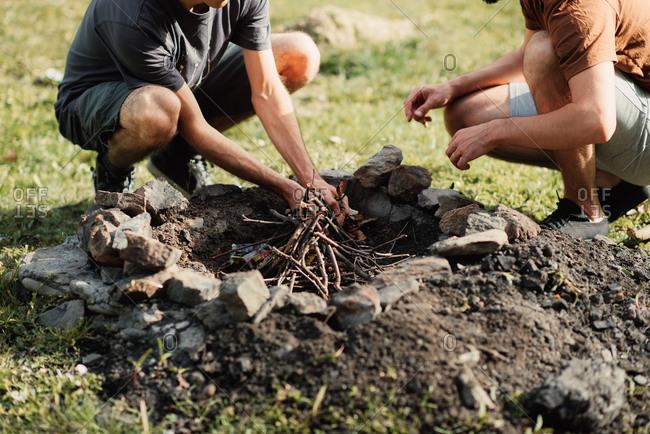 Two men starting a bonfire