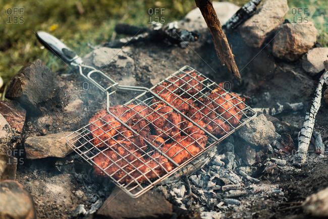 Seasoned meat cooking on a bonfire