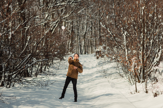Young man throwing a snow ball on a wooded trail