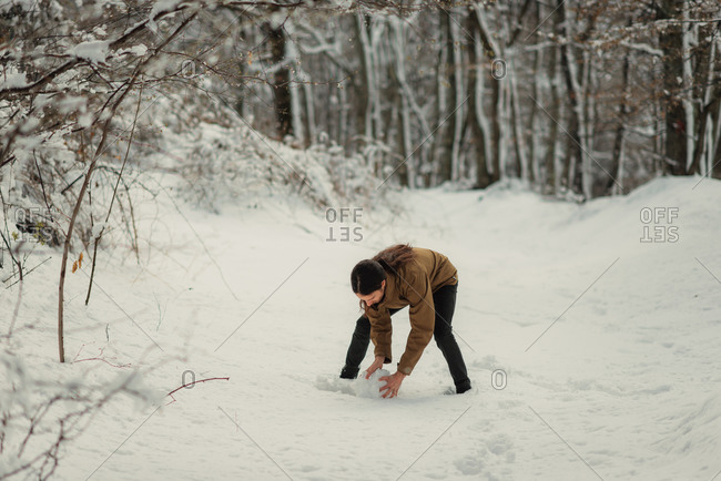 Young man bending over to make a snow ball on a wooded trail
