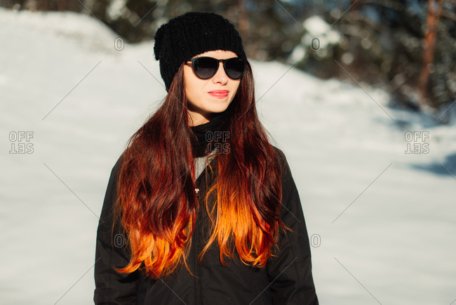 Woman with bright auburn hair standing on a snowy slope