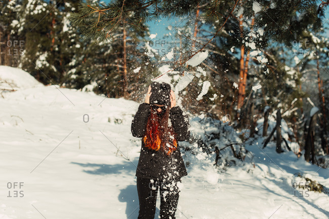 Woman on a snowy slope dodging a snowball