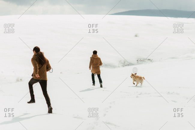 Two men running across a snowy landscape with a dog