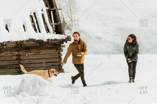 Man and woman playing with a dog on a snowy hillside