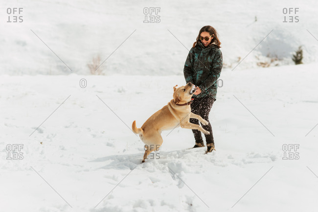 Young woman watching her dog catch a snowball