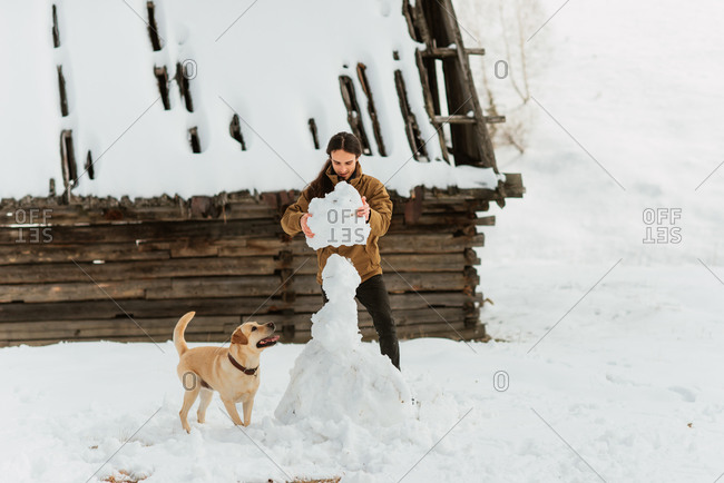 Man building a snowman on a hillside while his dog watches